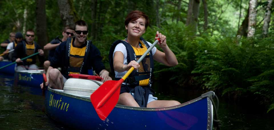 Group of people paddling in blue canoes and smiling to the camera