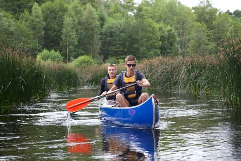 Two boys in a blue canoe from EMventure paddle on the river