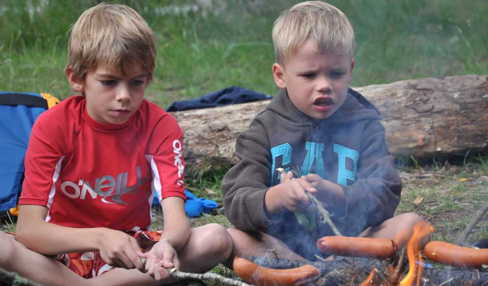 two boys grilling saucace by open fire