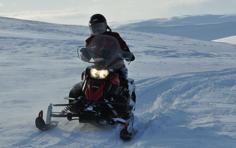Single snowmobile driving in the mountains