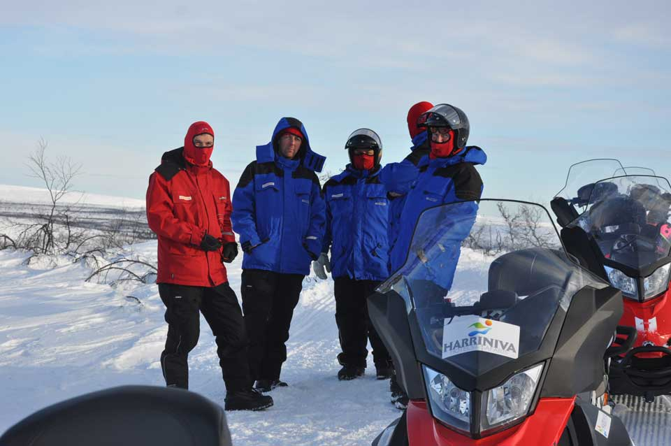 A group of snowmobiledrivers take a brake on the safari