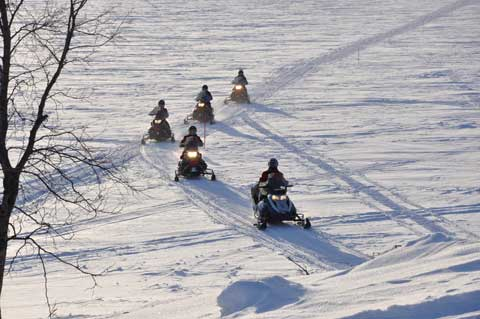 A group of snowmobiles drive on the trail in the mountains